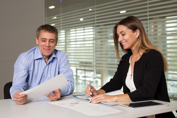 a man and a woman work in an office and talking