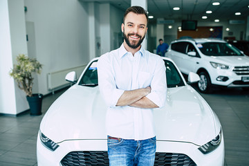 Happy handsome bearded man with crossed arms while buying a car in dealership