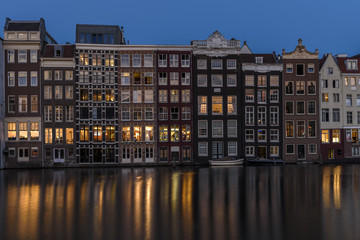 Tall buildings in Amsterdam, at disk, with the lights from the windows reflecting on the calm water of the canal