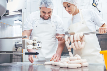Team of butchers, woman and man, filling sausage in meat industry