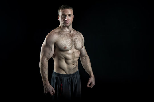 Pure perfection. Man bodybuilder posing with tense muscles on black background. Bodybuilder achieved best shape for muscles. Ready for championship. Bodybuilder perfect muscular body, copy space