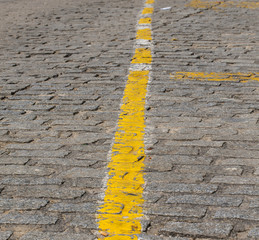 Texture of dark grey cobblestones with yellow stripe as road marking