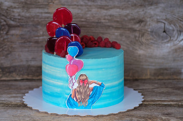 beautiful home cake with blue cream, decorated with balloons and colorful candy