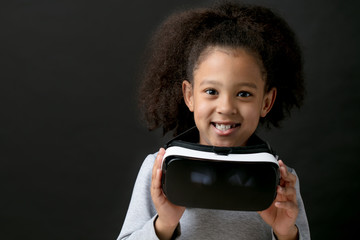 Little positive metis girl holding VR glasses. isolated black background.technology concept.free time. entertainment.