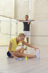 Lady stretching leg out on badminton court