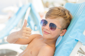 the boy on a sunny beach lies on a sun lounger in sunglasses and showing thumbs up