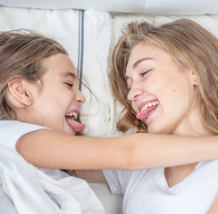 Mother and daughter on the bed looking at each other and grimaced
