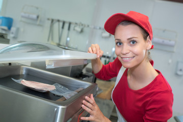 portrait of happy saleswoman holding meat packages at counter