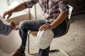 close up cropped side view photo. builder in casual outfit sitting on the chair and holding the hardhat
