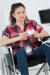 Disabled girl playing computer game, looking forlorn