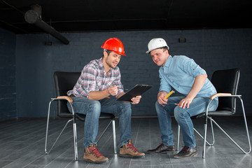 two talented workers in hardhats are looking at the documents indoors. full length photo
