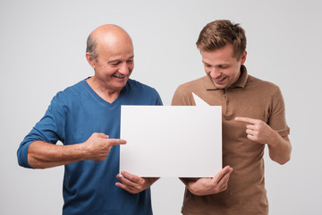 Two mature men father and son are holding a white empty billboard together