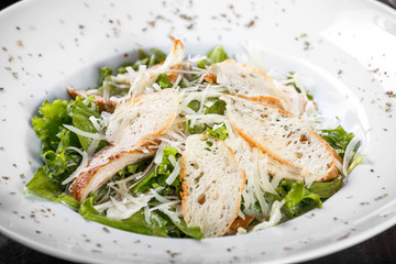 Salad with chicken breast, parmesan cheese, croutons, mixed greens, lettuce on wooden background. Healthy food