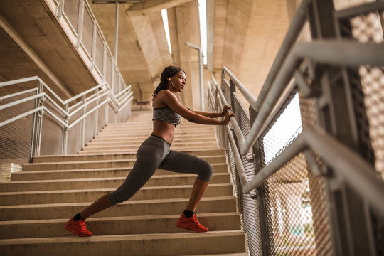 Young black athletic girl doing stretching exercise on stairs