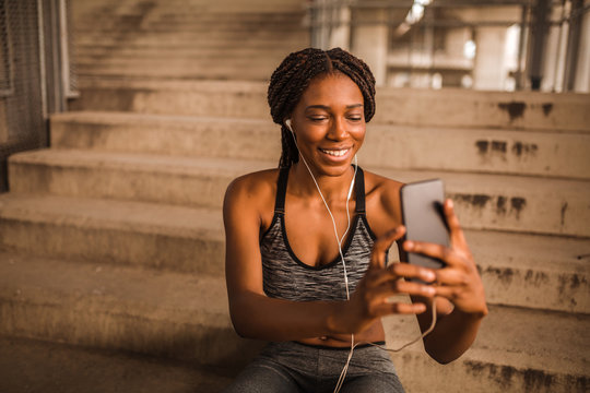 Young black woman with earphones in sportswear is sitting on stairs and taking selfie