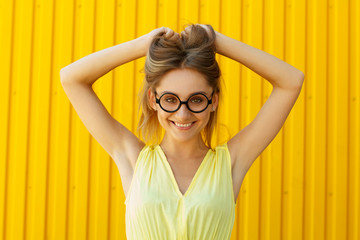Portrait of a joyful girl wearing toy funny glasses over yellow background at daylight