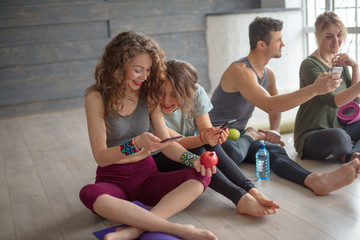 Cheerful fit young co-workers in sportswear having rest and drinking water after workout on floor before going home. People, body shape, health, wellbeing and active lifestyle concept.