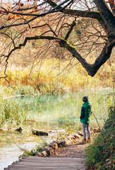 Boy stay near pond in autumn park, last sunny autumn days