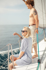 Attractive caucasian couple of loving man and woman enjoying privateness on pleasure. Yacht in open sea sitting, sunbathing and talking with each other on yacht deck. Sea Travel Vacation