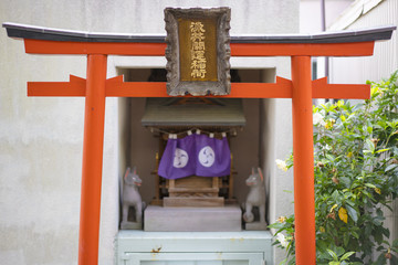 Shinto neighborhood sanctuary with torii portal dedicated to Inari fox deity in Komagome's Somei Ginza shopping street.