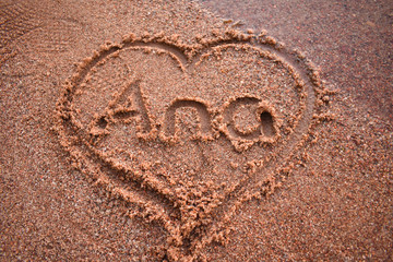 Name inside a heart written on the sand