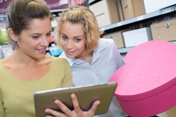 two female friends using tablet in a shop