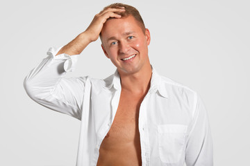 Cheerful young male with friendly smile, healthy skin, keeps hand on head, wears elegant shirt, shows muscular body, poses against white background. People, masculinity and emotions concept.