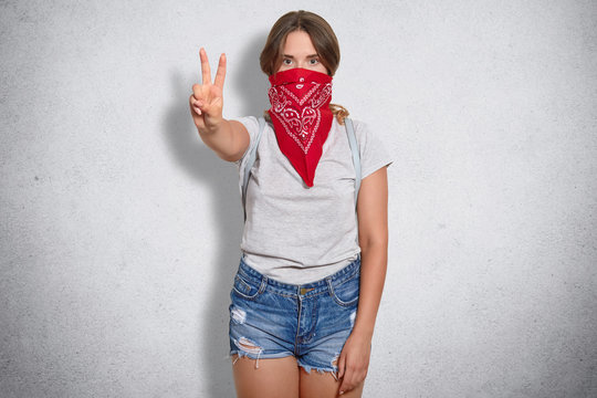Indoor shot of self confident female feminist shows peace sign, wears fashionable red bandana, wears jean shorts and grey t shirt, isolated over grey background. All women are equal with men