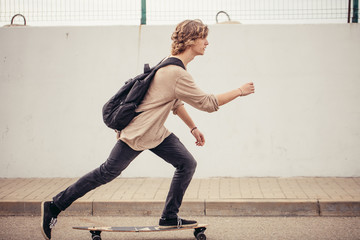 Young curly long haired man riding on longboard on empty road