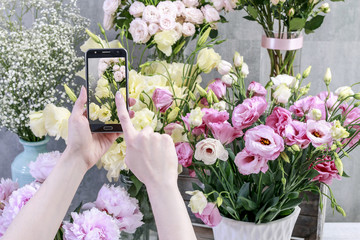 Flowers ordered online. Woman taking picture of plants by her smartpnone.