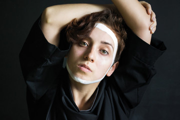 fashion photo portrait of a girl with curly short hair in black clothes with white paint around her face hands behind her head dark background