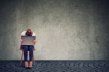 Sad woman with laptop on chair