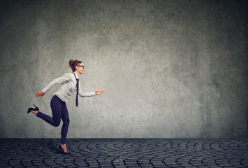 Businesswoman running against gray wall