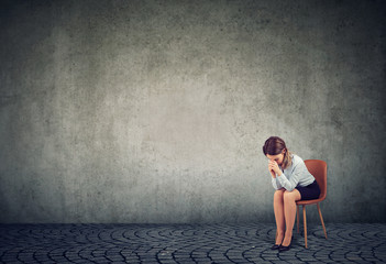Stressed and desperate woman sitting on chair