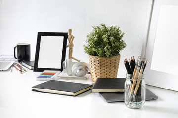 Artist workplace table with jar of pencil, sketch book, photo frame and plant decoration on white table.