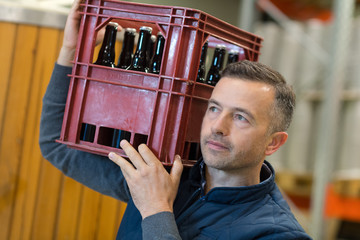 man carrying a box with wine bottles in wine store