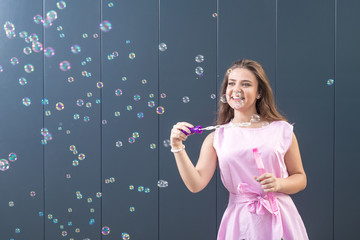 Teenage girl blowing soap bubbles against gray wall