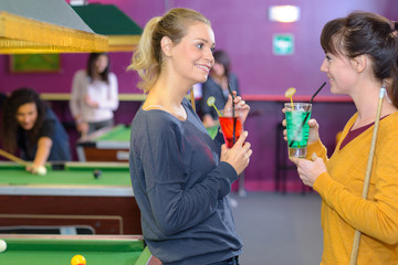 two female friends drinking and playing billiards