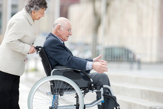 senior lady pushing her husband in his wheelchair