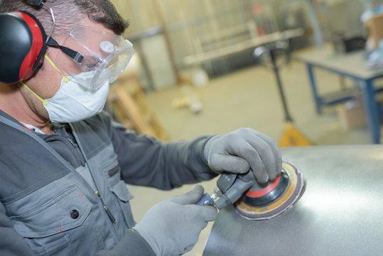 man holding sanding metalic surface