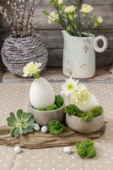Floral arrangement with goose egg, carnations, chrysanthemum and moss.