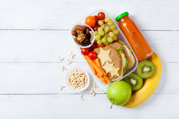 School lunch box with vegetables, fruits and sandwich for healthy snack on white wooden table top view. Fototapete