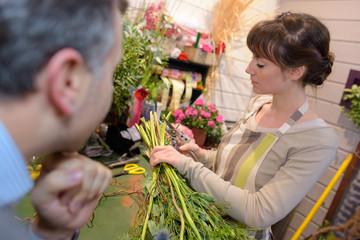 female florist preparing bouquet of flowers in flower shop