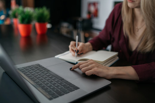 Female designer using laptop, sketching at blank notepad. Woman hand writing in notebook on wooden desk. Concept ease of use of Internet and accessibility of information of working process.