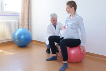 male doctor with pregnant woman sitting on fitness ball