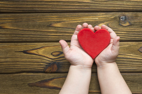 the child's hands hold a red heart