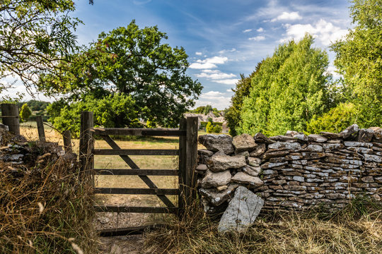 Wooden gate and stone wall along farmland, Cotswolds, England