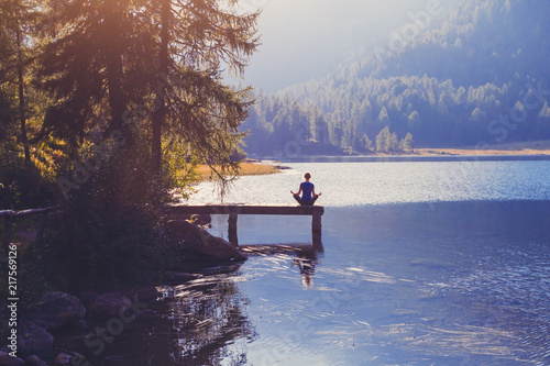 Wall mural meditation and yoga practicing at sunset, breathe exercise background with silhouette of woman, calmness and harmony