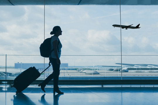 airport travel, silhouette of people at international departure terminal, flight