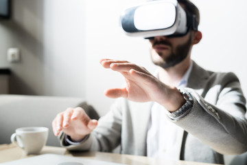 Manager in VR headset communicating with his virtual colleague at desk at office